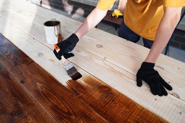 Ręka trzymająca pędzel nakładający farbę lakierniczą na drewnianą powierzchnię
