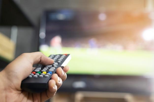 Ręka trzymająca pilota do telewizora