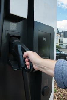 Ręka trzymająca pompę gazu w zbiorniku gazu. tankowanie paliwa, oleju, gazu - zamknij stację gazową lub elektryczną.