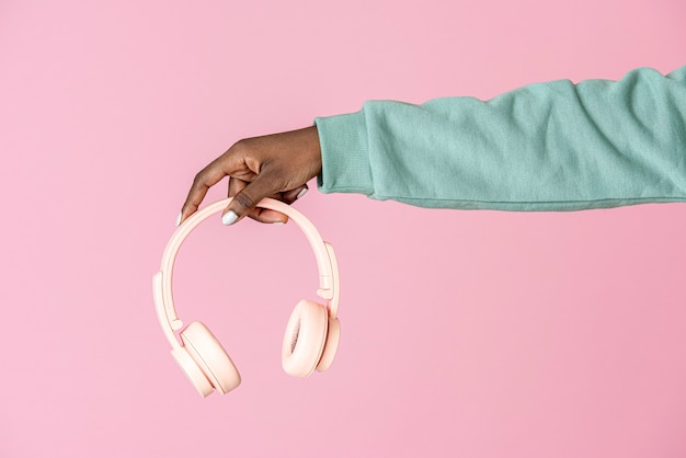 Ręka trzymająca różowe słuchawki