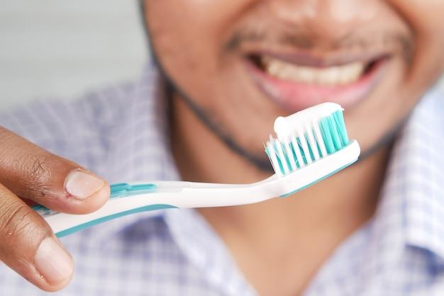 Ręka trzymająca szczoteczkę do zębów z pastą