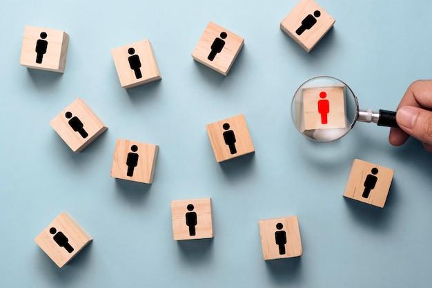 Ręka trzymająca szkło powiększające do wyszukiwania czerwona ikona człowieka na drewnianym bloku wśród czarnej ikony ludzi.