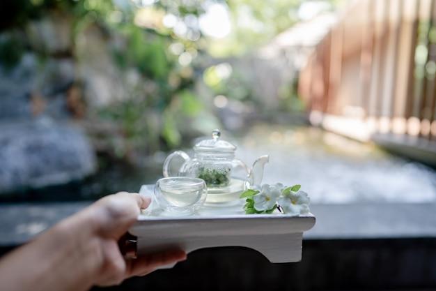 Ręka trzymająca tacę serwowała przezroczysty czajniczek z herbatą ziołową.