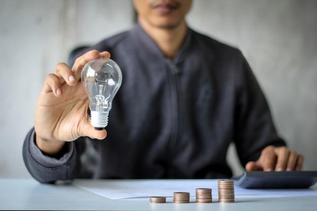 Ręka trzymająca żarówkę nad stosem monet
