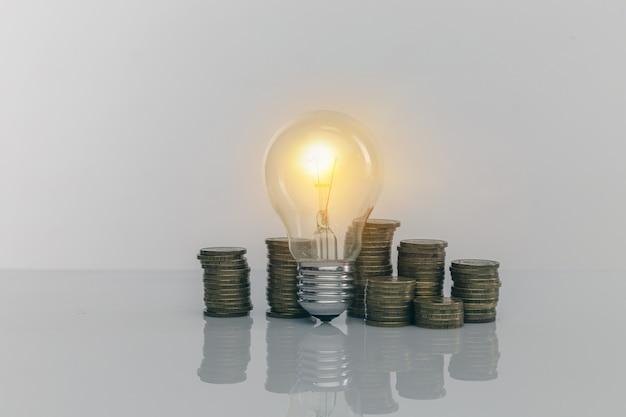 Ręka trzymająca żarówkę z stosem monet. kreatywne pomysły na oszczędzanie pieniędzy. zarządzanie pieniędzmi na przyszłość.