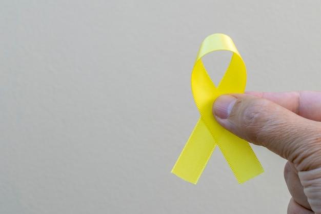 Ręka trzymająca żółtą kokardkę reprezentującą kampanię zapobiegania samobójstwom