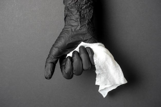 Ręka ubrana w czarną lateksową rękawiczkę trzyma białą szmatę na czarnym tle