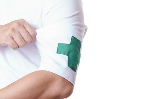 Ręka ubrana w zieloną krzyżową opaskę