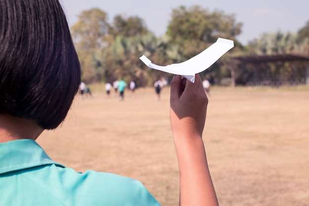 Ręka uczeń trzyma papierowego samolot w trzon edukaci klasie.