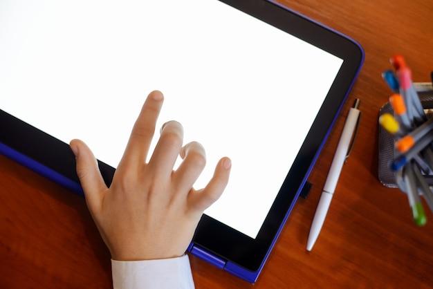 Ręka ucznia pracującego z dużym tabletem podczas kwarantanny w domu