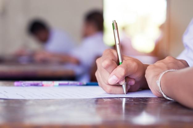 Ręka ucznie pisze egzaminie w sala lekcyjnej z stresem