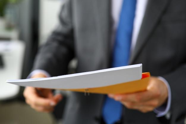 Ręka urzędnika w garniturze i krawacie z żółtą kopertą zawierającą partię ważnych dokumentów