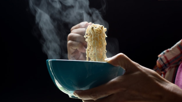 Ręka używa chopsticks smakowici kluski z kontrparą i dymią w pucharze na drewnianym tle