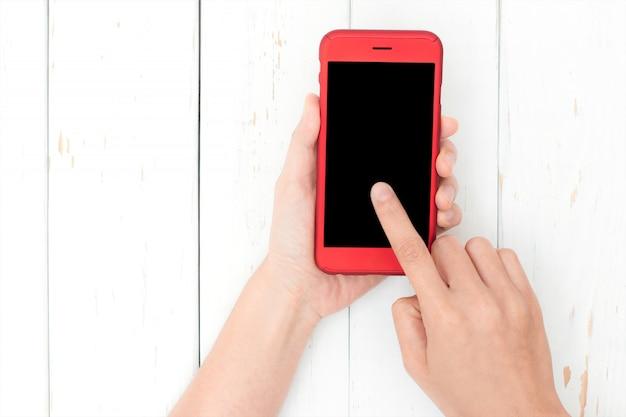 Ręka używać telefonu czerń ekran na odgórnym widoku. ten obraz ma ścieżkę przycinającą w sekcji ekranu.
