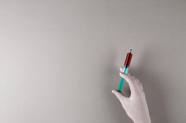 Ręka w białej gumowej rękawicy trzymając strzykawkę z próbką krwi
