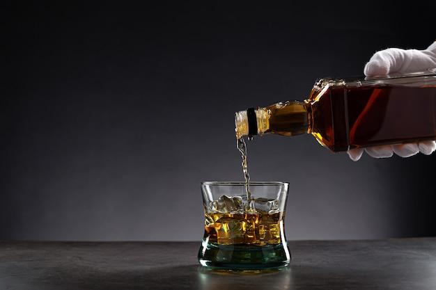 Ręka w białej rękawiczce nalewająca whisky do szklanki z lodem na ciemno