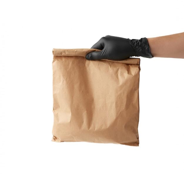 Ręka w czarnej lateksowej rękawicy mieści pełną papierową torbę z brązowego papieru rzemieślniczego, koncepcję zdalnej i bezdotykowej dostawy żywności