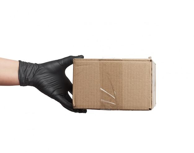 Ręka w czarnej lateksowej rękawicy trzyma kartonowe pudełko z brązowego papieru pakowego na białej przestrzeni