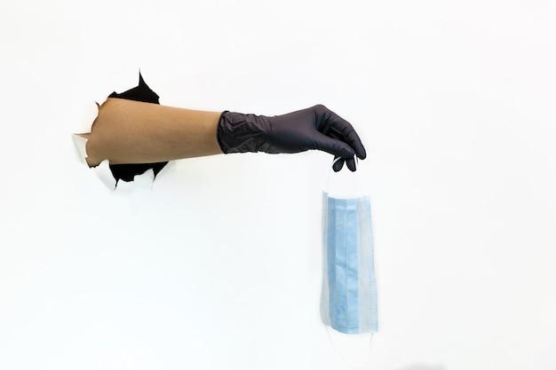 Ręka w czarnej lateksowej rękawiczce w rozdartej dziurze na białym tle trzyma maskę na twarz. środki kwarantanny zapobiegające rozprzestrzenianiu się covid 19. ręka w rękawiczce przez rozdarty papier