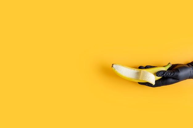Ręka w czarnej rękawiczce trzyma banana na żółtym tle. sztuka żywności