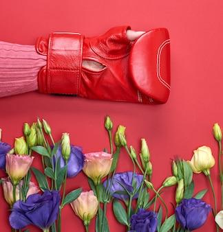 Ręka w czerwonej rękawicy bokserskiej i kwiaty eustoma lisianthus