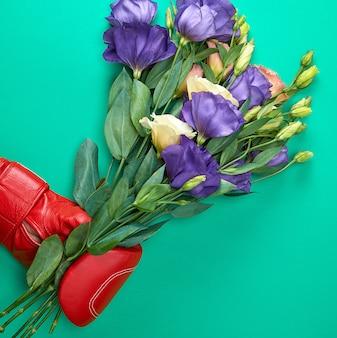 Ręka w czerwonej rękawicy bokserskiej z bukietem kwiatów eustoma lisianthus
