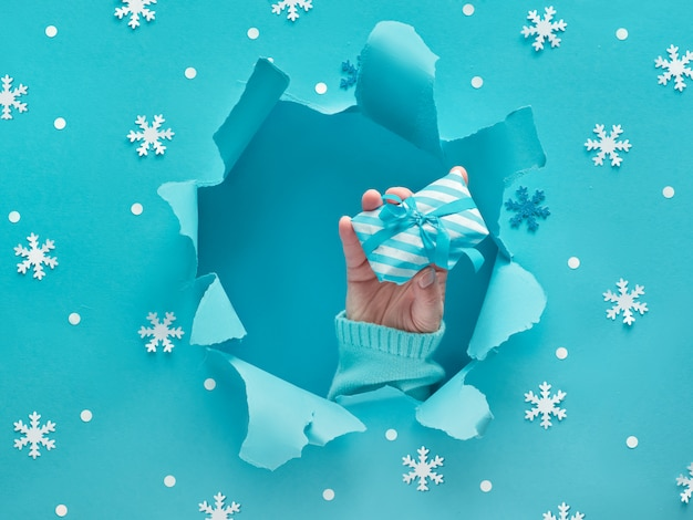 Ręka w dziurze z pudełkiem prezentowym w zgranej papierowej dziurze, niebieska ściana mięty z płatkami śniegu