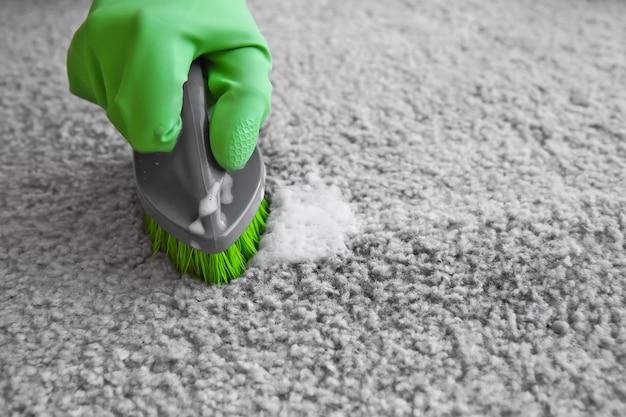 Ręka w gumowej rękawicy do czyszczenia dywanów z pędzelkiem, z bliska