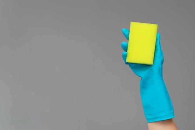 Ręka w gumowej rękawicy posiada kolorową gąbkę do mycia