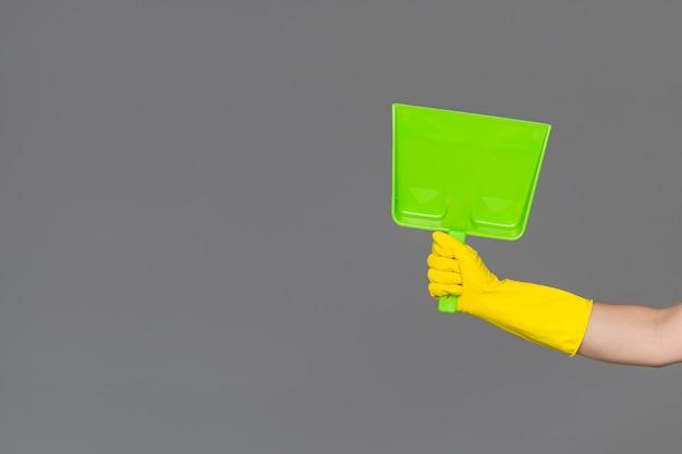 Ręka w gumowej rękawicy trzyma łyżkę na neutralnym