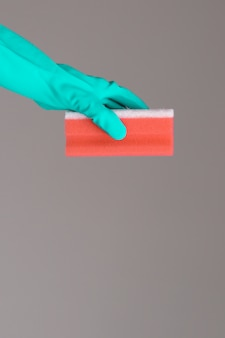 Ręka w gumowej rękawicy utrzymuje gąbkę do mycia kolorów na neutralnej powierzchni. koncepcja jasnej wiosny.