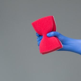 Ręka w gumowej rękawicy utrzymuje kolorową gąbkę do mycia na neutralnym.