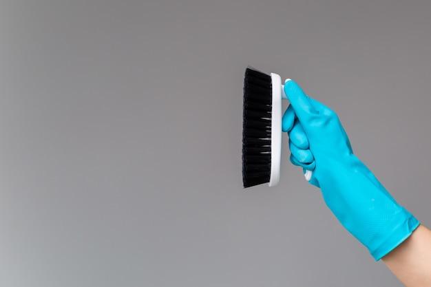 Ręka w gumowej rękawicy utrzymuje szczotkę do mycia naczyń