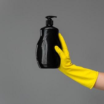 Ręka w gumowej rękawicy zawiera butelkę detergentu do mycia naczyń