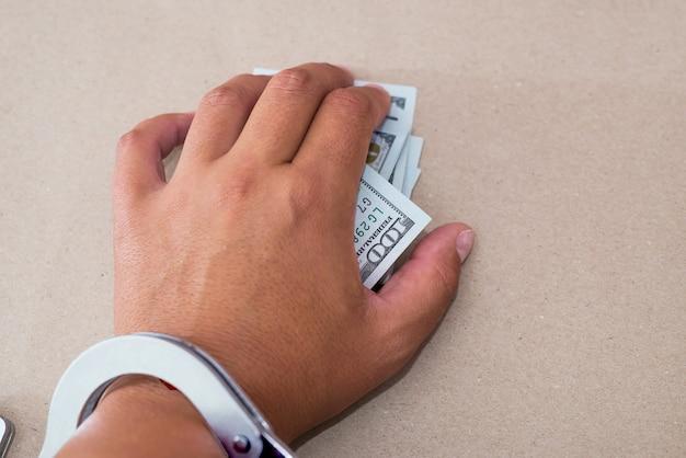 Ręka w kajdanki trzymając banknoty dolarowe. mężczyzna skuty kajdankami z łapówką