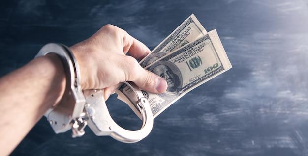 Ręka w kajdanki trzymająca pieniądze