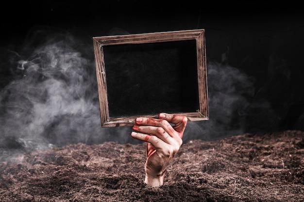 Ręka w krwi wtyka z ziemi i trzyma czarny znak