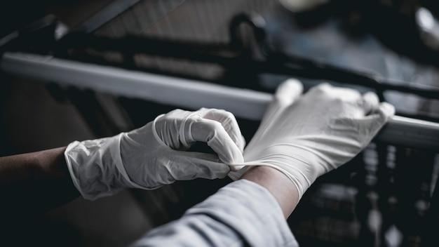 Ręka w lateksowej rękawiczce podczas pchania koszyka, aby zapobiec zakażeniu koronawirusem