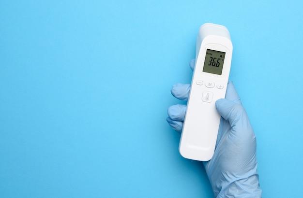 Ręka w niebieskich rękawiczkach lateksowych trzyma elektroniczny termometr do pomiaru temperatury, urządzenie bezdotykowe, wyświetlacz pokazuje temperaturę 36,6 stopni