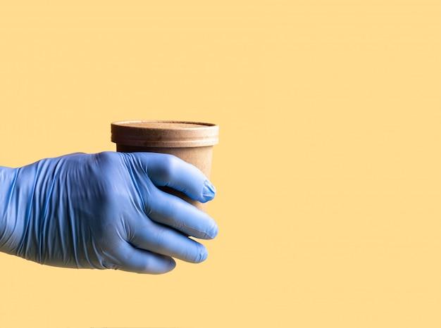 Ręka w niebieskich rękawiczkach ochronnych trzyma papierowy kubek jednorazowy