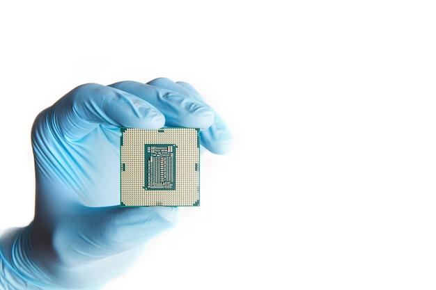 Ręka w niebieskich rękawiczkach trzyma mikroprocesor, z bliska