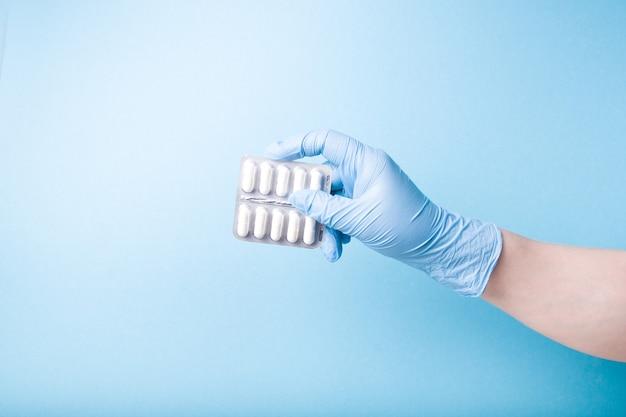 Ręka w niebieskiej jednorazowej rękawicy medycznej trzyma blister z białymi kapsułkami na niebieskiej powierzchni