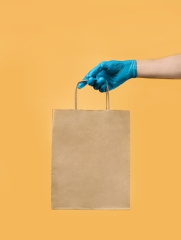 Ręka w niebieskiej lateksowej rękawicy trzyma worek rzemieślniczy. koncepcja bezpiecznej dostawy.
