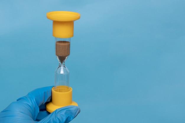 Ręka w niebieskiej rękawicy ochronnej trzyma klepsydrę na niebieskim tle, zbliżenie, kopia przestrzeń. zrozumienie terminów i środków kwarantanny dla koronawirusa