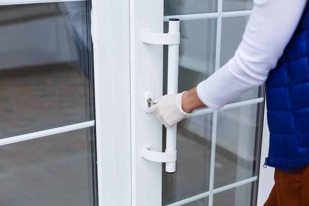 Ręka w niebieskiej rękawiczce medycznej otwiera drzwi. koncepcja higieny.