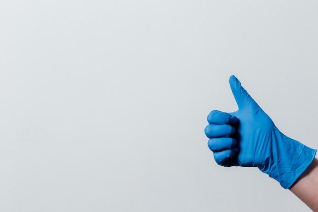 Ręka w rękawicach medycznych pokazuje.