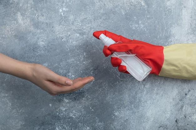 Ręka w rękawicach ochronnych rozpylająca etanol na kobietę.