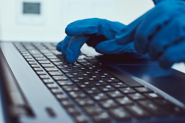 Ręka w rękawice ochronne, wpisując na klawiaturze laptopa. cyberprzestępczość i ochrona informacji koncepcja