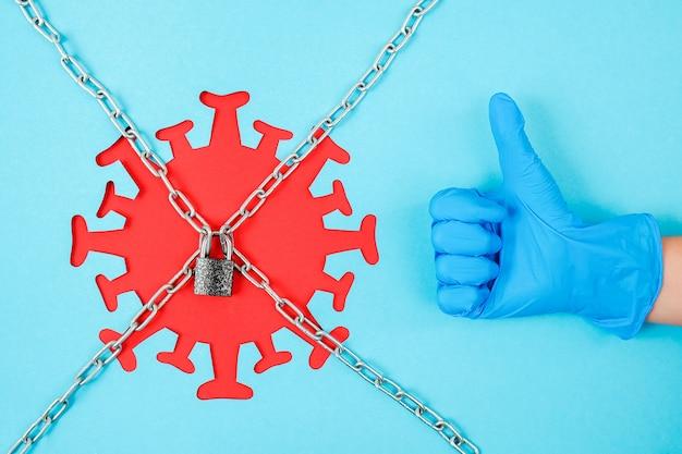 Ręka w rękawicy medycznej pokazuje jak gest i czerwony koronawirus, wirus, bakterie, drobnoustroje za łańcuchami i zamkniętym zamkiem