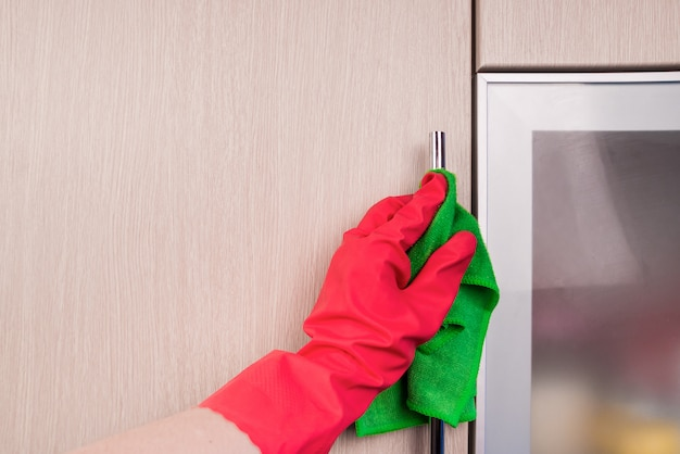 Ręka w rękawicy ochronnej do czyszczenia drewnianych mebli szmatką. wczesne porządki wiosenne lub regularne sprzątanie. pokojówka sprząta dom.